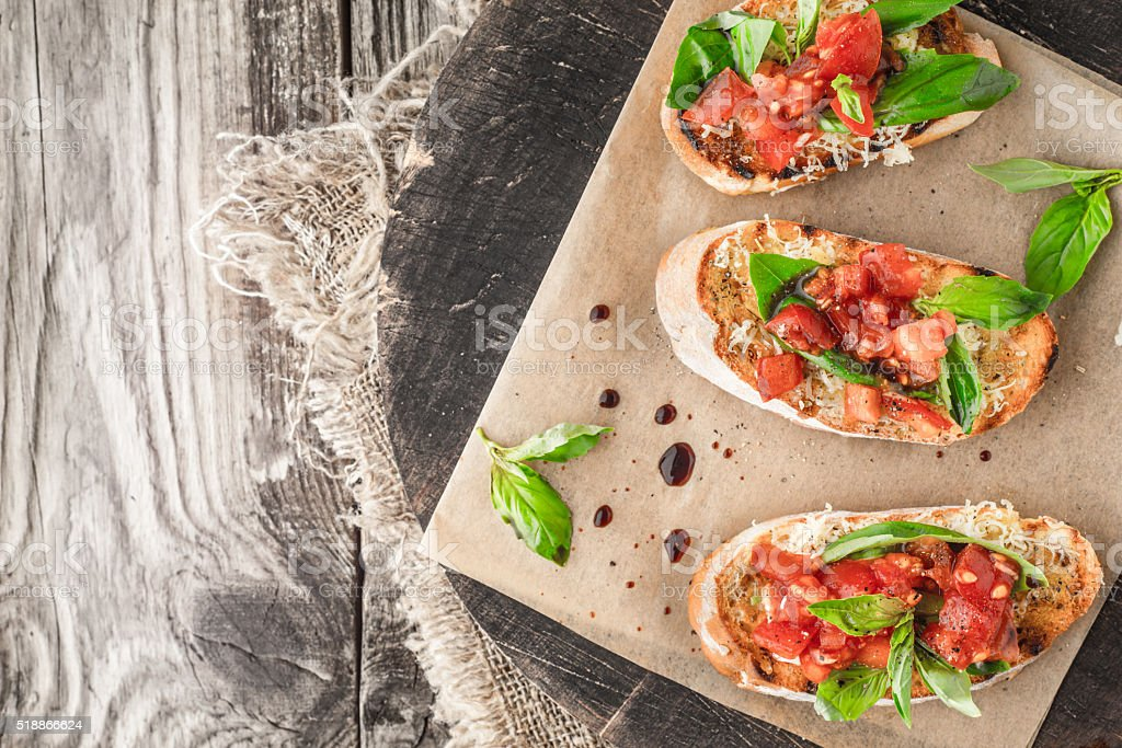 Bruschetta with tomatoes and basil on  wooden board top view stock photo