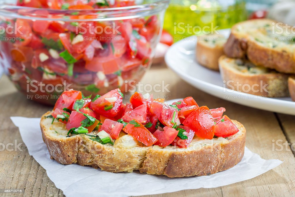 Bruschetta with tomatoes, herbs and oil on garlic cheese bread stock photo