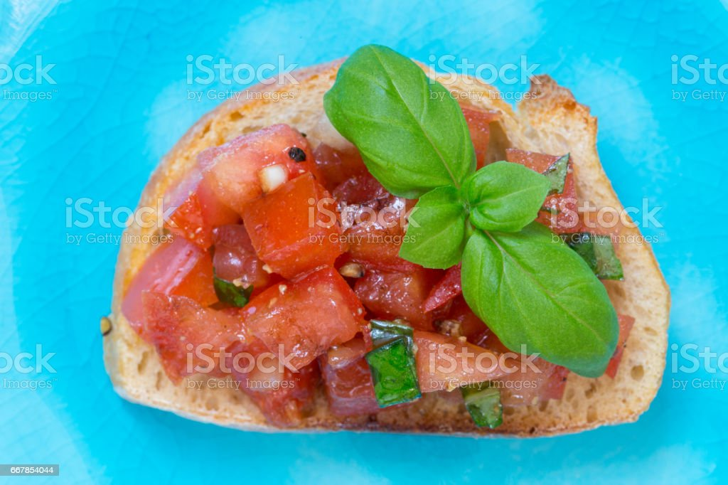 Bruschetta with tomatoes on a turquoise plate stock photo
