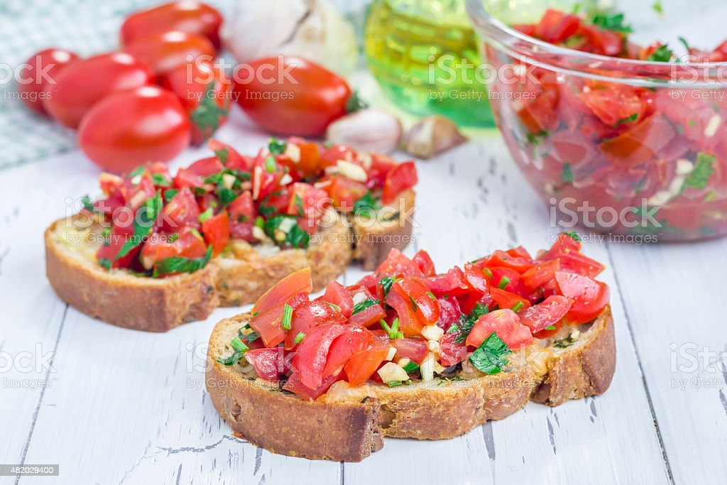 Bruschetta with tomatoes on toasted garlic cheese bread stock photo