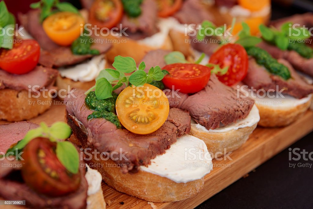 Bruschettas with beefsteak and pesto sauce stock photo