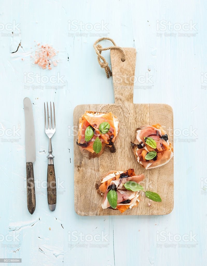 Bruschettas with Prosciutto, roasted melon, soft cheese and basil on stock photo