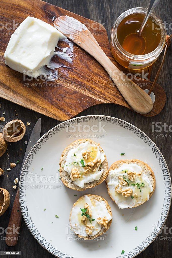 Bruschette with italian Stracchino cheese, honey, walnuts and thyme stock photo