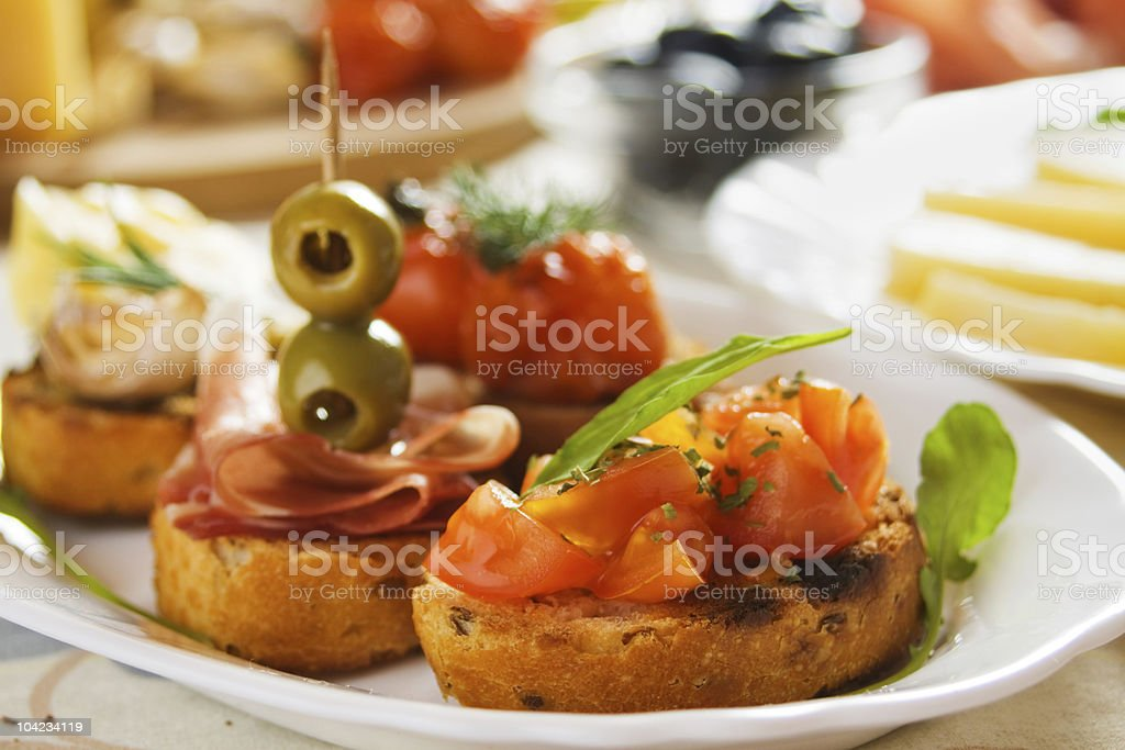 Bruschette with tomato, olives and prosciutto royalty-free stock photo