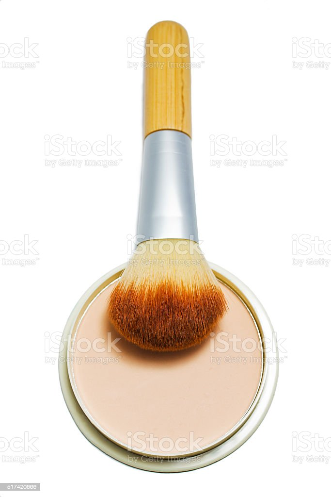 Brush and compact powder beige color isolated on white background stock photo