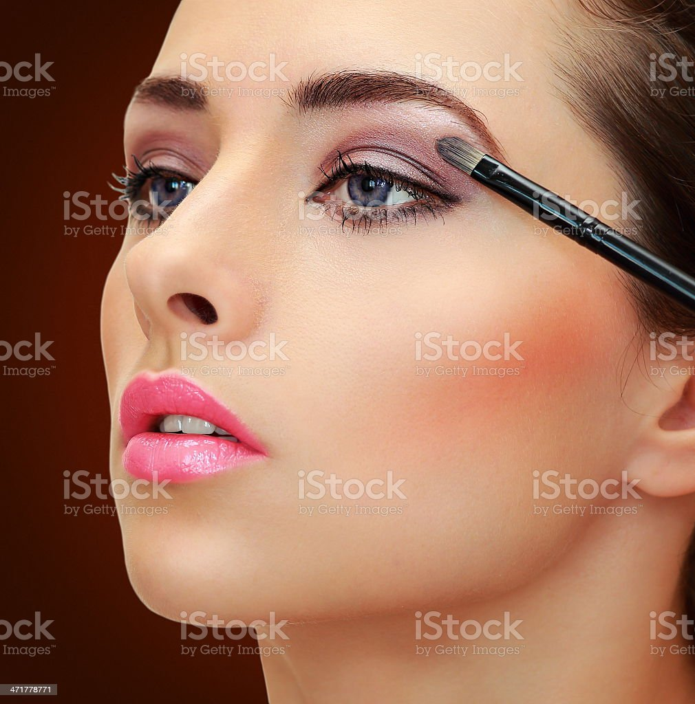 Brush applying eye shadows on beauty woman face. Closeup portrait stock photo