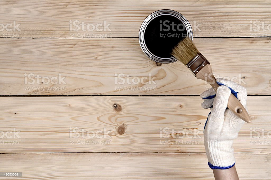Brush in hand and painting on the wooden wall stock photo