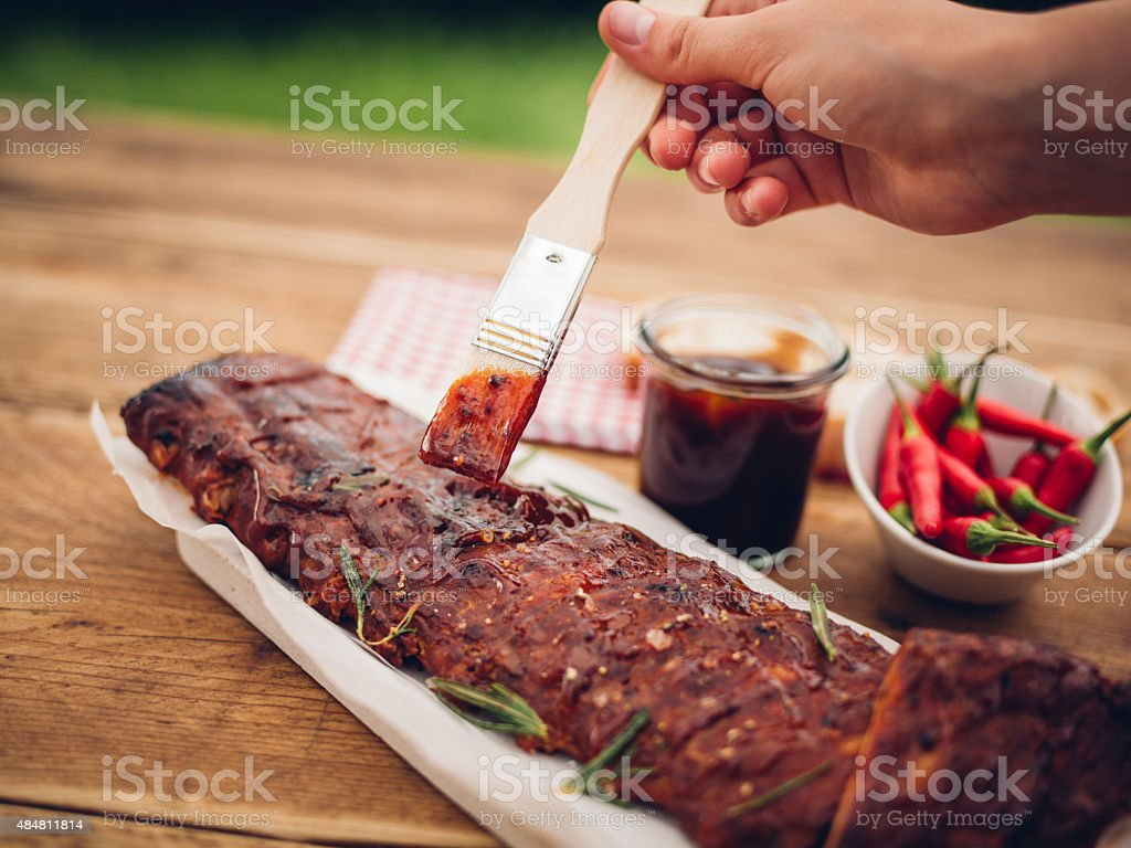 Brush painting barbecue sauce onto a rack of ribs stock photo