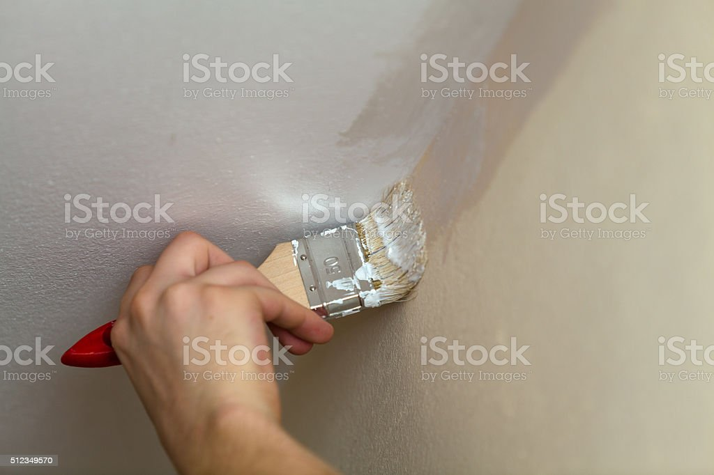 Brush weld the walls with the ceiling white paint. stock photo