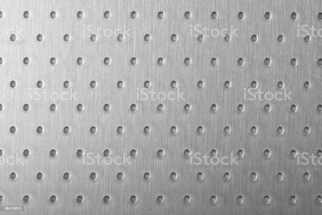 brushed metal with perforation punch stock photo