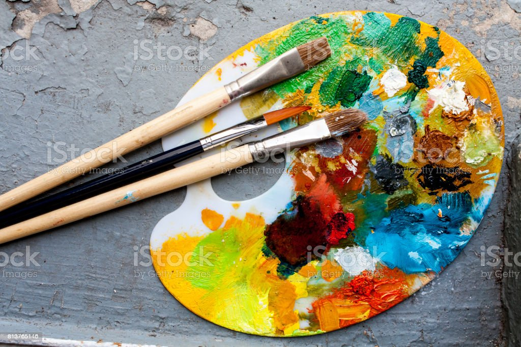 Brushes and colorful abstract oil colors paiters pallet, grunge background stock photo
