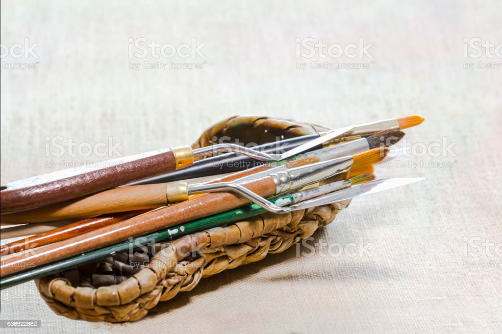 Brushes and palette knifes in wicker bast on canvas stock photo