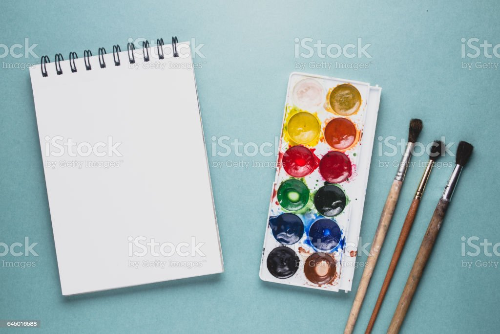 Brushes and watercolor on the green background. Creativity concept stock photo