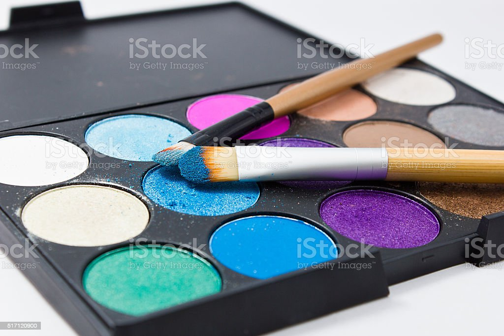 Brushes for make-up on the eye shadow palettes stock photo