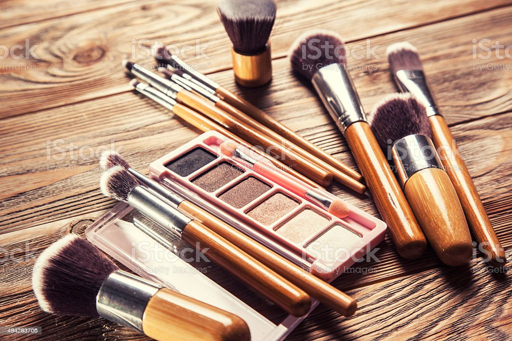 Brushes with cosmetics scattered chaotically stock photo