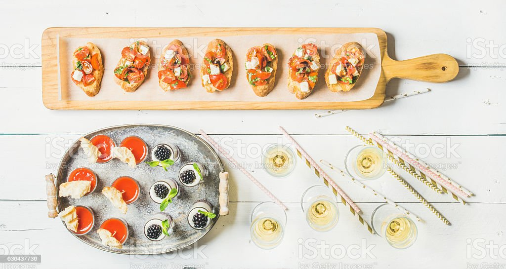 Brushettas, gazpacho shots, desserts, champagne and straws over white background stock photo