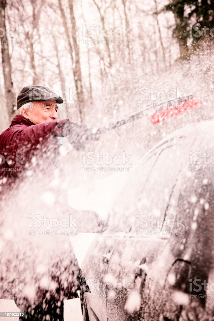 Brushing Winter snow off the car stock photo