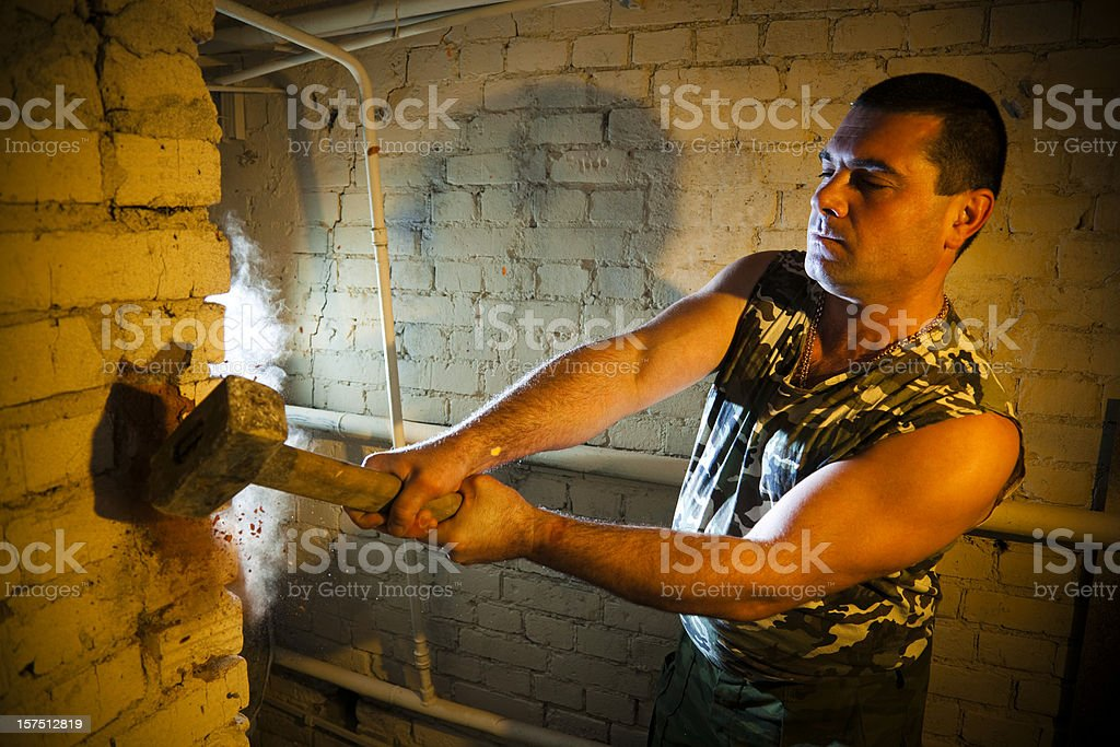 Brutal construction worker destroying brick wall with sledgehammer royalty-free stock photo