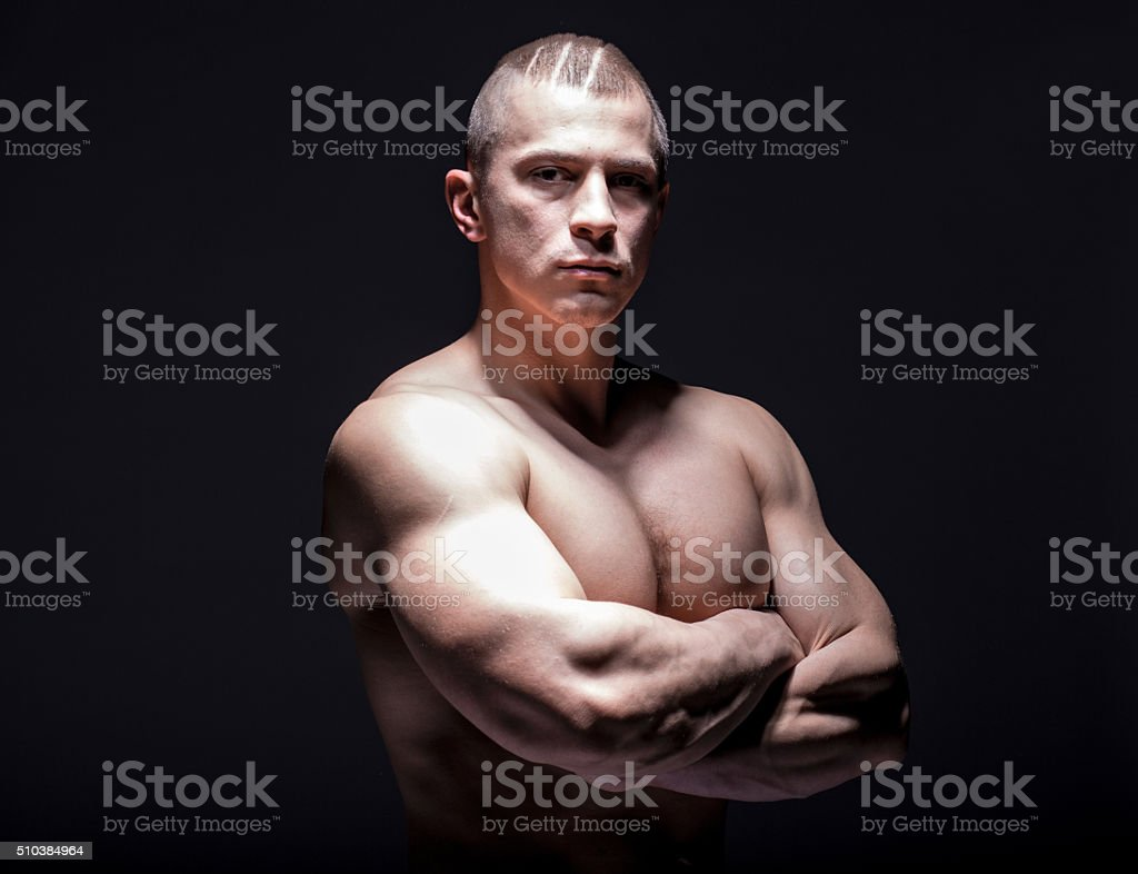 Brutal pumped muscular man on black background stock photo
