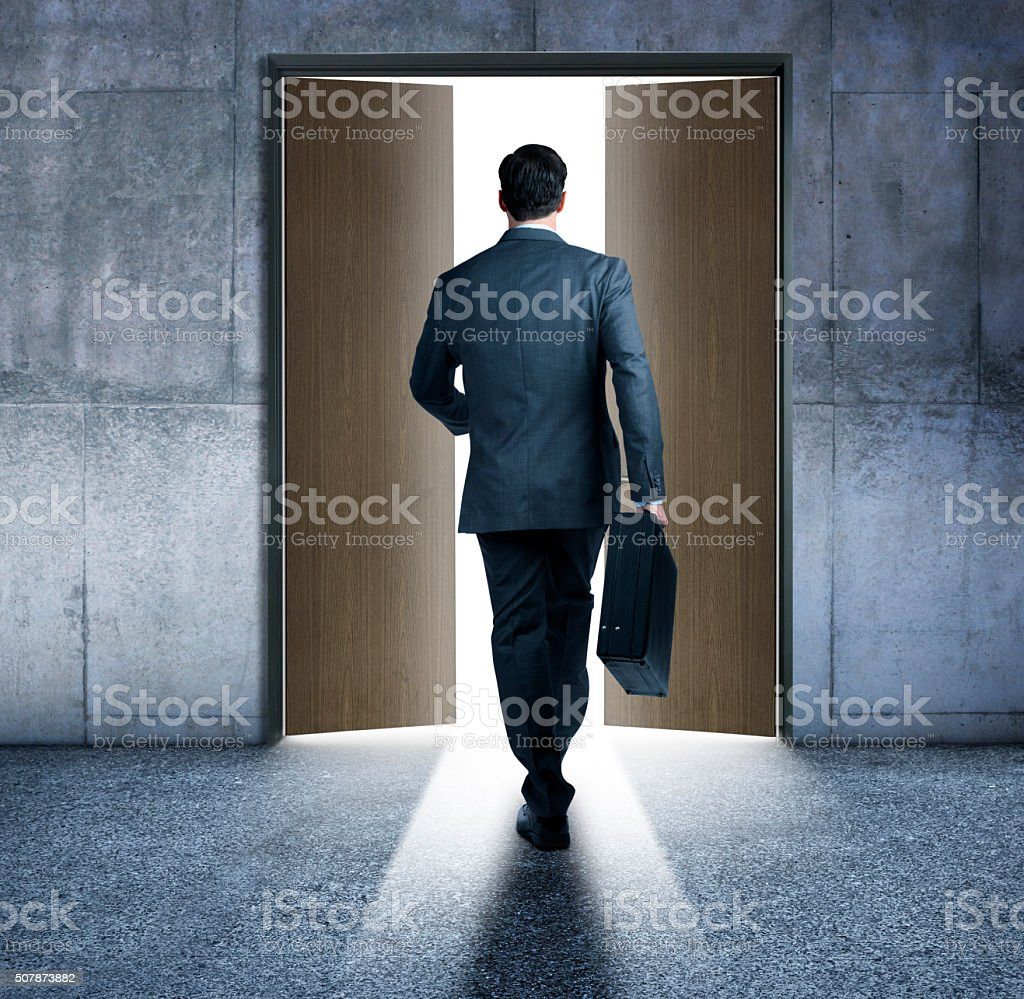 Bsuinessman About To Walk Through Open Doors stock photo