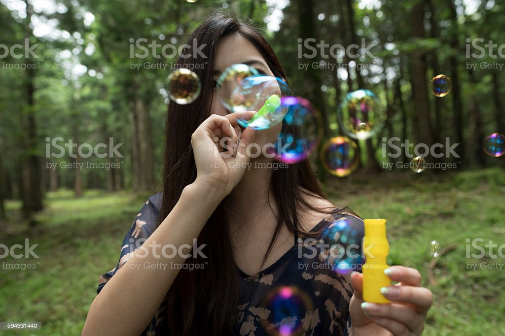 Bubbles and cute girl in the forest. stock photo