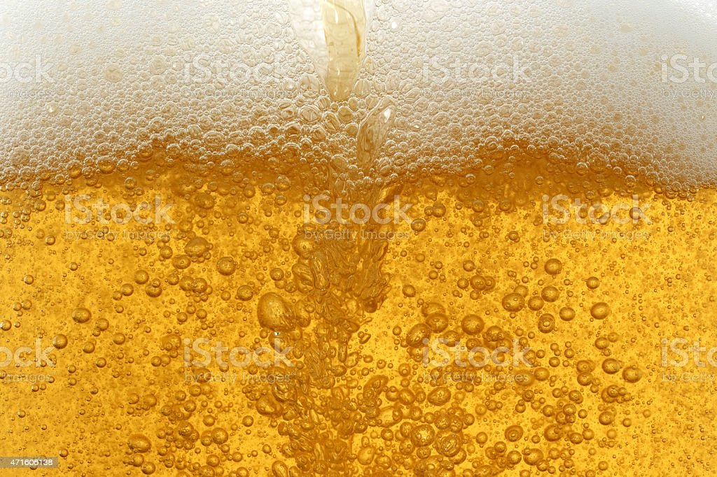 Bubbles and foam in glass of beer stock photo