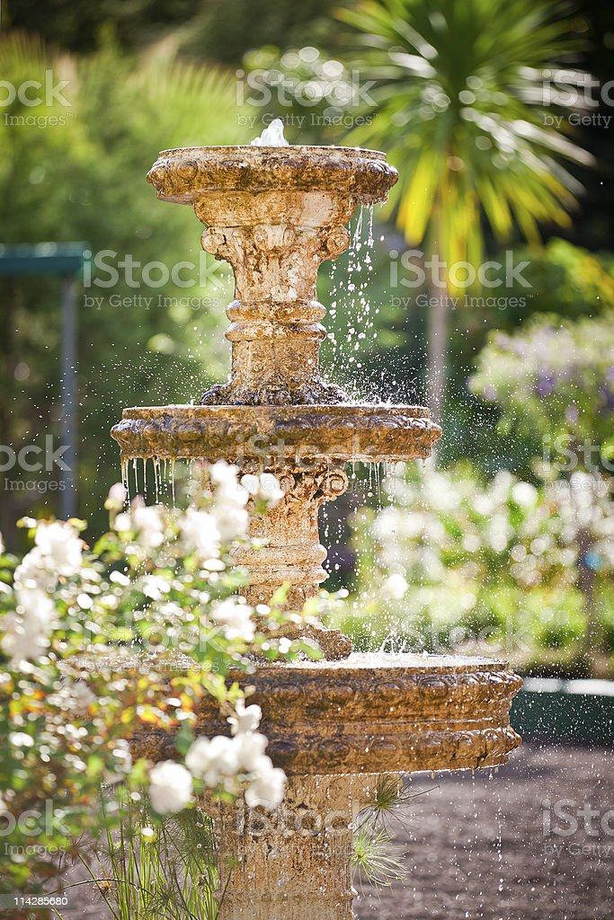 Bubbling fountain in courtyard garden stock photo