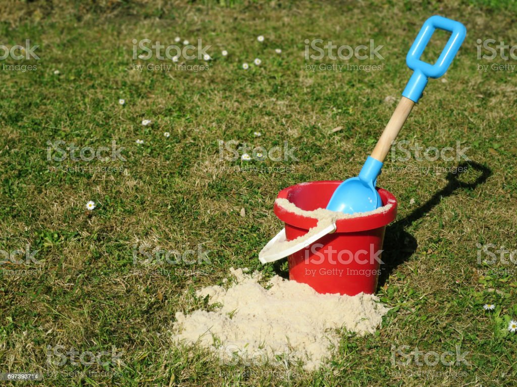 Bucket and spade (sand pail and shovel) on lawn, with small amount of sand. stock photo