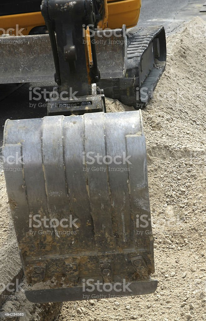 bucket of a bulldozer during the digging in the road stock photo