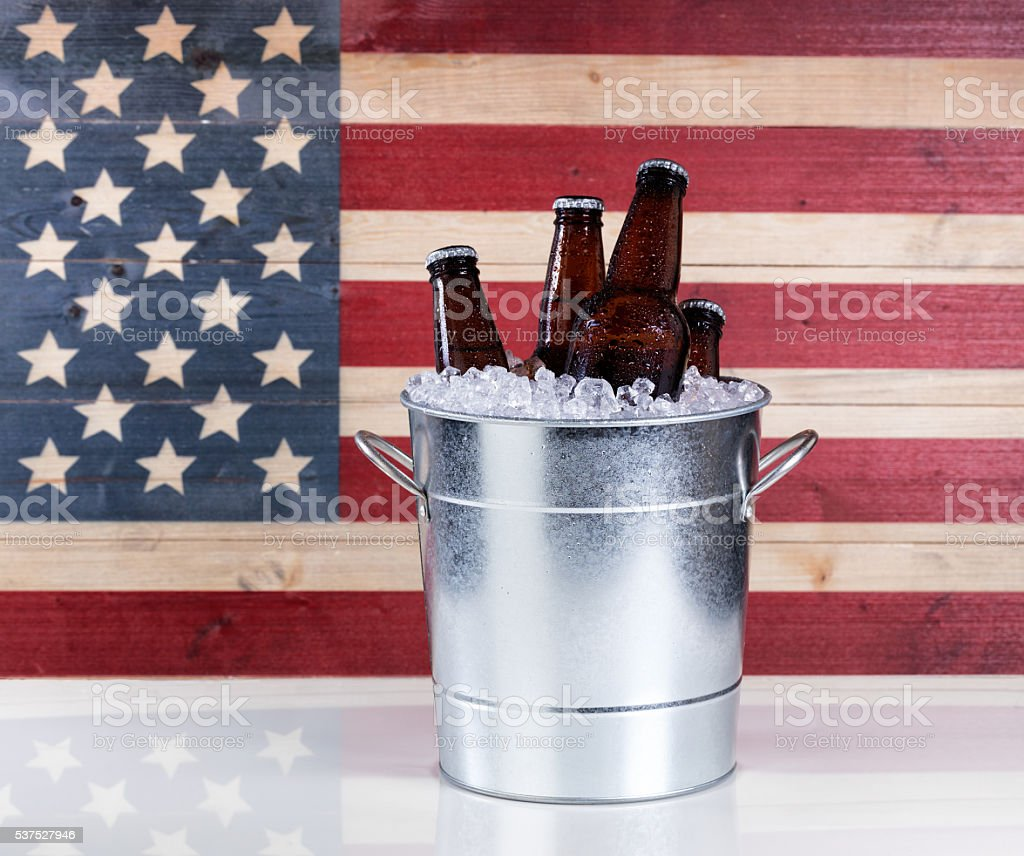 Bucket of ice cold beer with USA flag in background stock photo