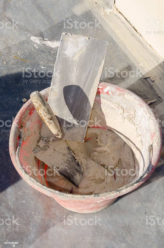 bucket with cement and tools stock photo