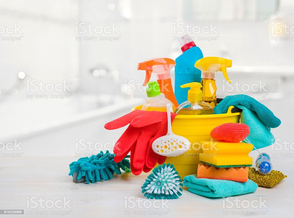 Bucket with chemical products on table over blurred bathroom background stock photo