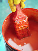 Bucket with red paint with paintbrush
