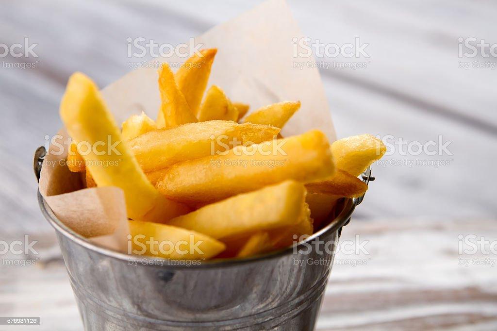 Bucket with yellow fries. stock photo