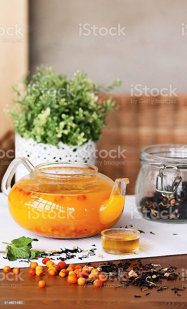 buckthorn tea in a teapot on the table stock photo