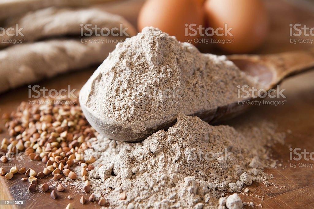Buckwheat flour overflowing on wooden spoon stock photo