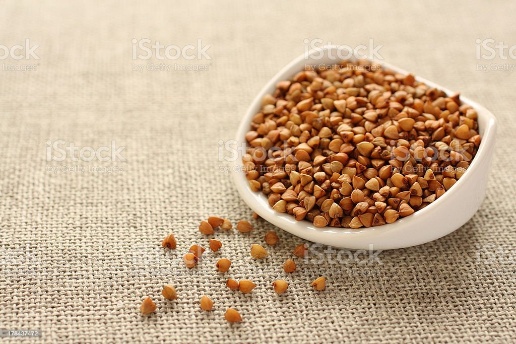 Buckwheat grains in white ceramic bowl on sackcloth background royalty-free stock photo