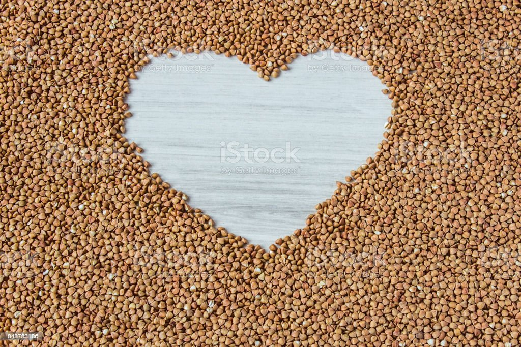 Buckwheat groats in a heart shaped bowl on white wooden background stock photo