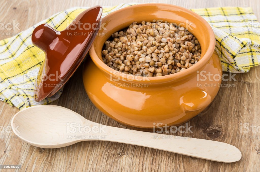 Buckwheat in pot, lid, wooden spoon and napkin on table stock photo