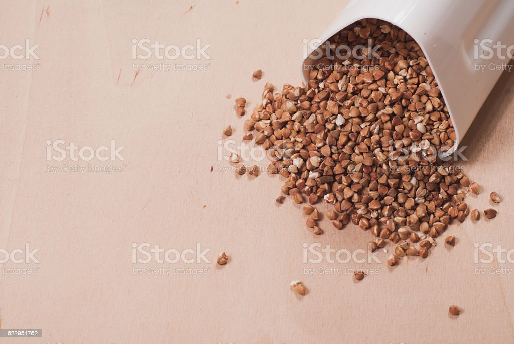 Buckwheat is scattered from the white container, stock photo