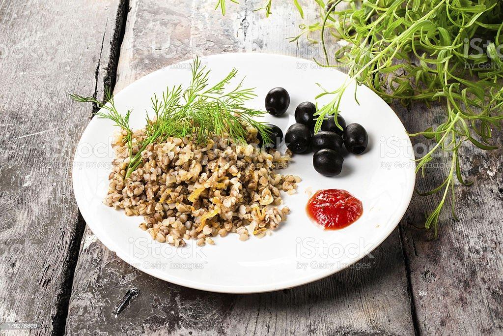 Buckwheat porridge, black olives and herbs royalty-free stock photo