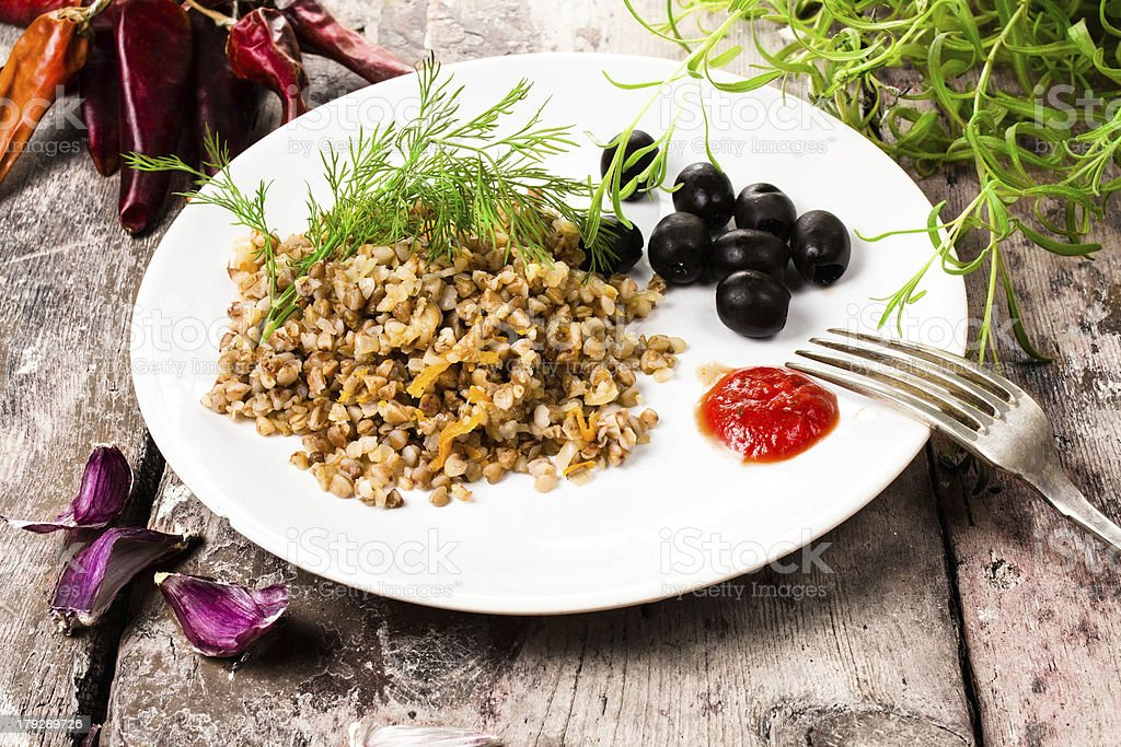 Buckwheat porridge, garlic, black olives and herbs royalty-free stock photo