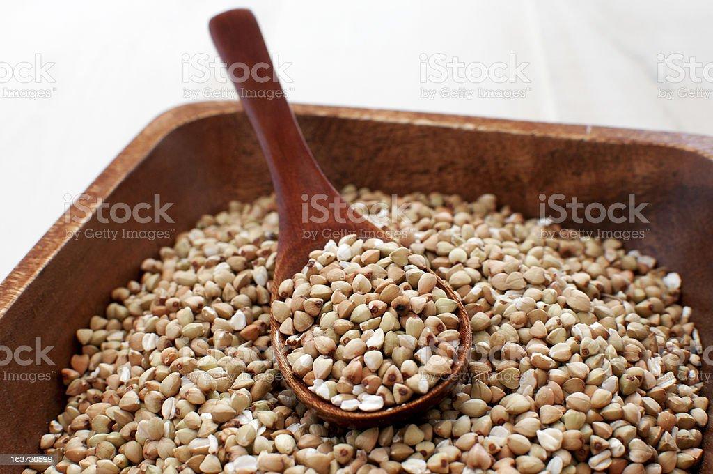 Buckwheat seeds closeup in wooden spoon stock photo