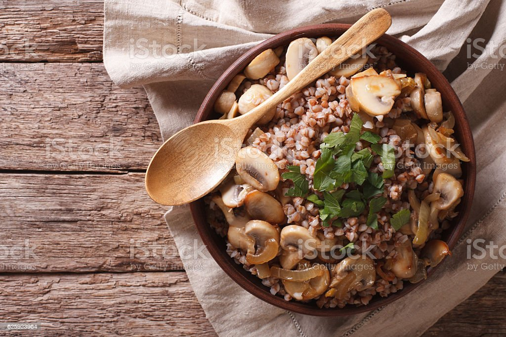 Buckwheat with roasted mushrooms and onions in a bowl. horizontal stock photo