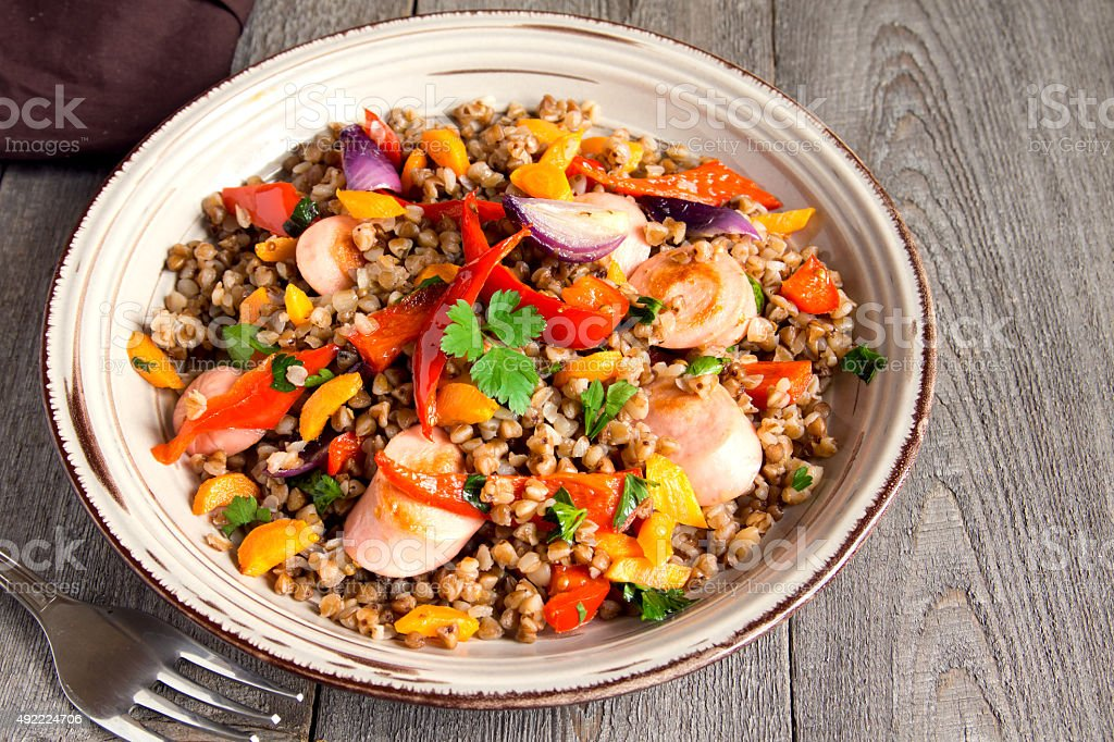 Buckwheat with sausages and vegetables stock photo