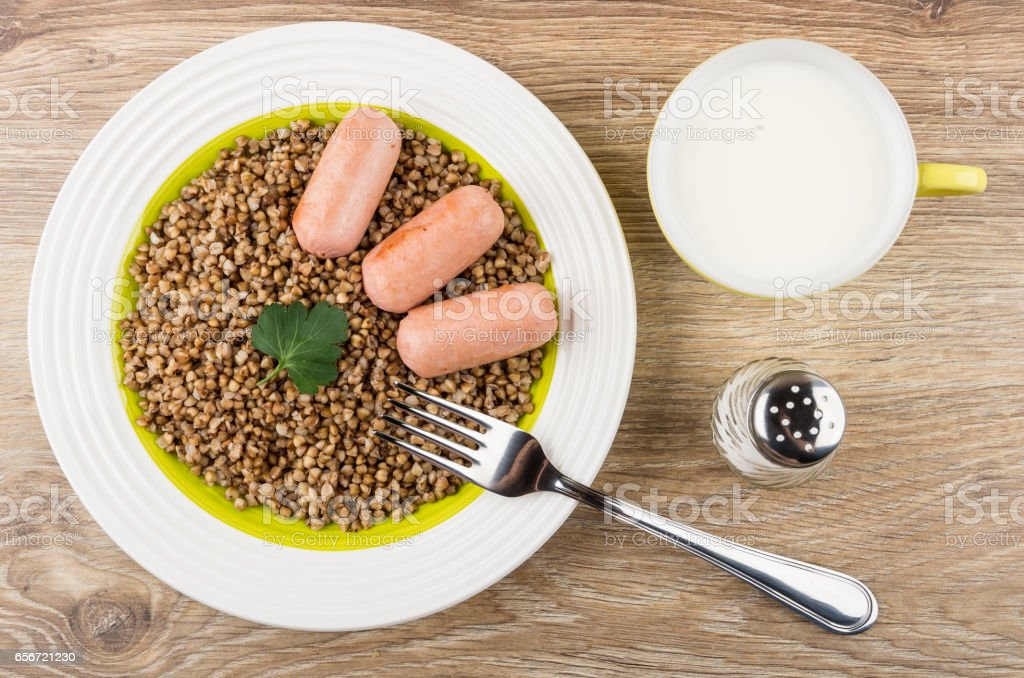 Buckwheat with sausages in plate, milk, salt and fork stock photo