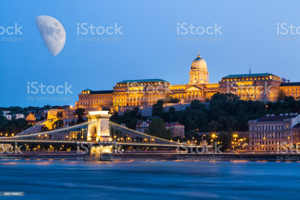 Budapest during blue hour - Szechenyi Chain Bridge, that spans the River Danube between Buda and Pest and Buda Castle with moon in the sky stock photo
