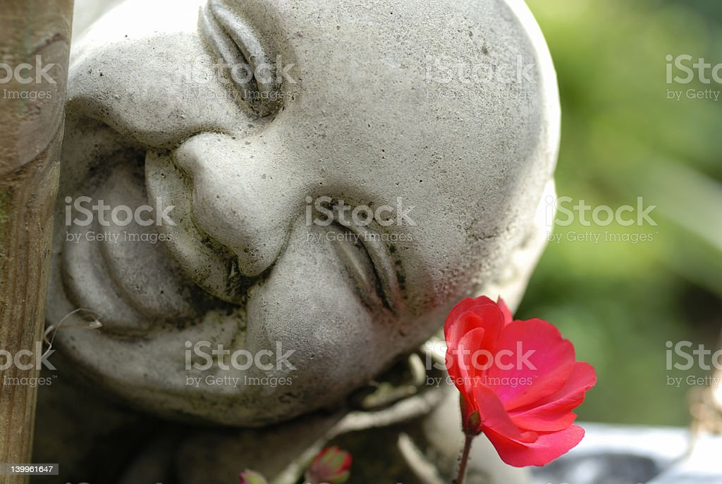 Buddha Backlit against Green Foliage stock photo