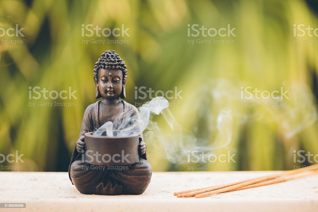 Buddha figurine with incense stock photo
