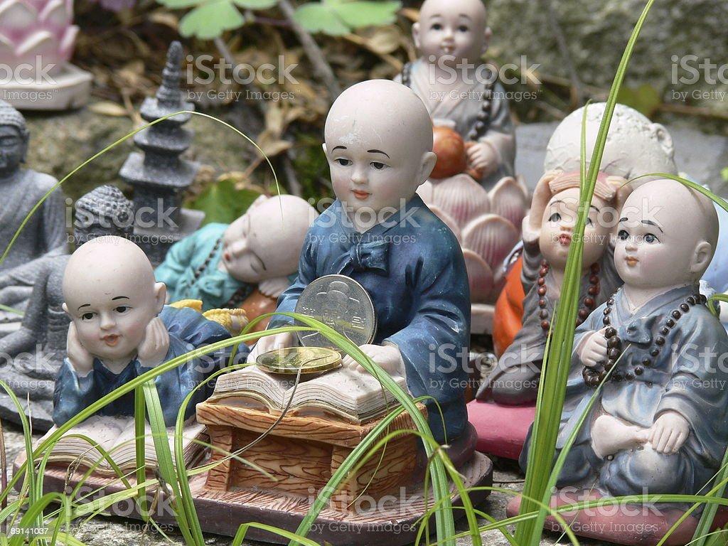 buddha figurines in the grass stock photo